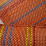 Orange pillow with blue, yellow and red